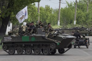 Pro-Russian armed men ride on top of an armoured personnel carrier near the town of Slaviansk
