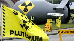 Greenpeace activists prepare a symbolic inflated nuclear bomb at a mock checkpoint on a road from Cherbourg and the COGEMA nuclear reprocessing plant of La Hague, September 30, 2004. Two ships, the Pacific Teal and the Pacific Pintail, transporting 140 kg of [weapons]-grade plutomium, left the US September 20 and are soon due to arrive in Cherbourg. The nuclear waste will be conditioned here before being transported from this Northwestern french port some 1200 kms by road to a plutonium fuel fabrication facility in Cadarache, Southern France. - RTXMYPO